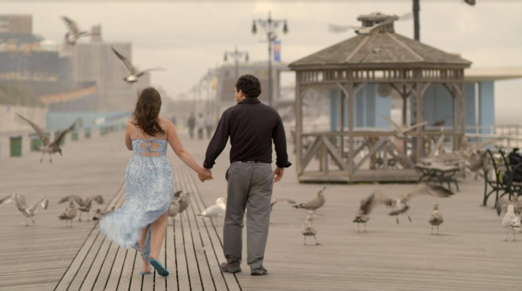 [COURTESY OF KEEP THE CHANGE] - image shows the two lead actors from behind as they walk down the boardwalk holding hands.