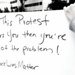 "Image description: image is a white cardboard protest sign with the words written in black ink, ""If this protest bothers you then you're part of the problem #BlackLivesMatter"""